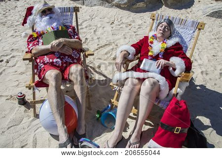 Santa And Mrs Claus Sleeping With  Books On Beach