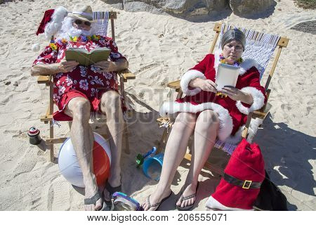 Santa And Mrs Claus Reading Books On Beach