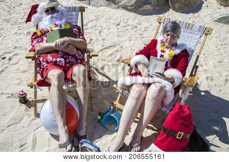 Santa And Mrs Claus Reading Books And Napping On Beach