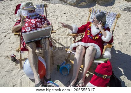 Santa Claus Working On Laptop Computer And Mrs Claus On Phone On Sandy Beach