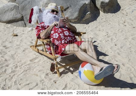 Santa Claus Using Tablet Or E-reader On Beach