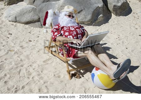 Santa Claus Typing On Beach With Laptop Computer On Vacation