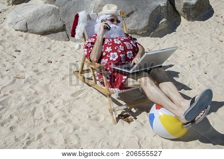 Santa Claus Talking On The Phone On Beach Chair With Laptop Computer On Vacation