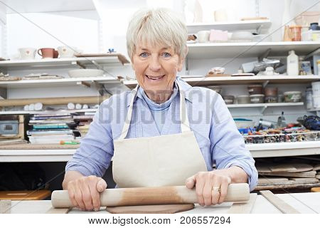 Portrait Of Senior Woman Rolling Out Clay In Pottery Studio
