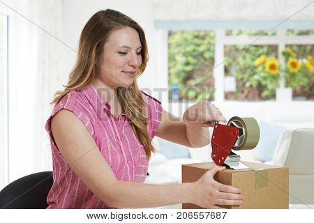 Woman At Home Sealing Box For Dispatch