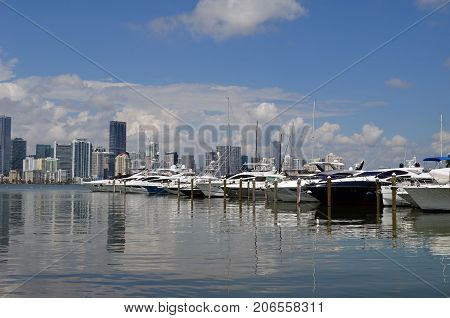A variety of pleasure boats moored at a marina on Key Biscayne,Florida with Miami high rise building skyline in the background