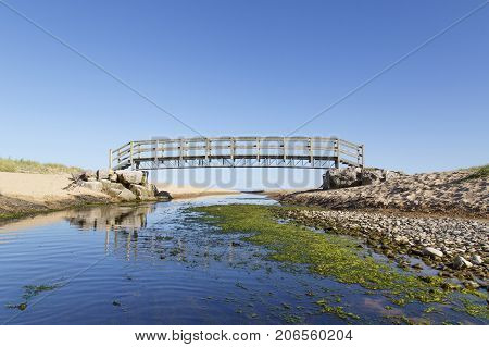 Footbridge over a coastal inlet with summer blue skies and flowing water at Oxwich on the Gower Peninsular