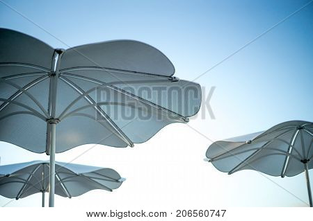 Patio umbrellas against sky behind moakley courthouse on waterfront in boston seaport harbor