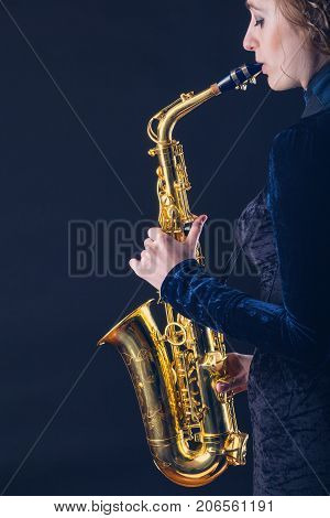 Saxophone player. Woman with saxophone against a dark background