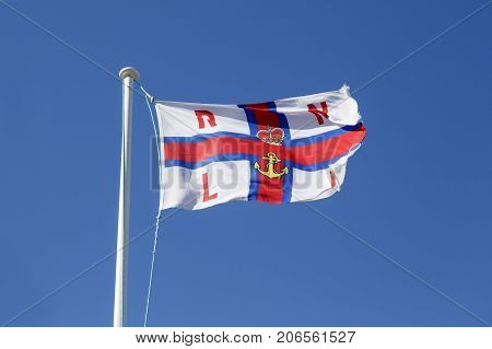 Port Isaac, Cornwall, UK: April 14, 2016: RNLI (Royal National Lifeboat Institution) flag flying outside the Port Isaac inshore lifeboat station.