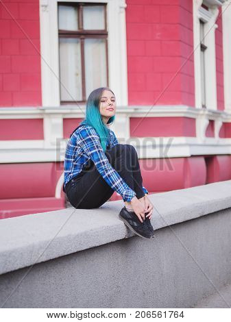 Hipster girl with blue dyed hair. Woman with piercing in nose, ears tunnels and unusual hairstyle having fun, posing in European city. Carefree concept. poster