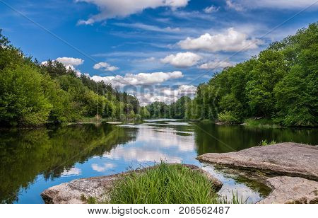 Summer landscape of the river blue sky with clouds reflections in the water woods and stones. The river Ros Ukraine.