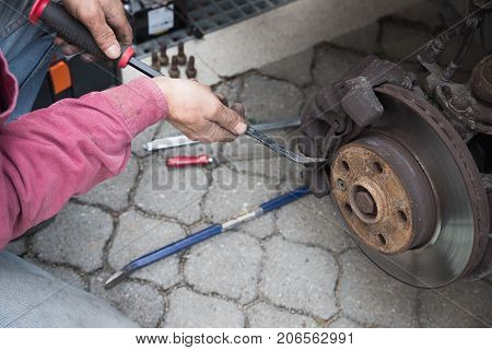 Man Repairing A Car - Opening The Brake Calliper For Change The Lining