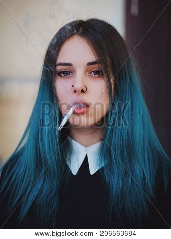 Emo girl smoking cigarette. Young student or pupil with blue colorful dyed hair, hat, piercing, lenses, ears tunnels and unusual hairstyle stands on black background.
