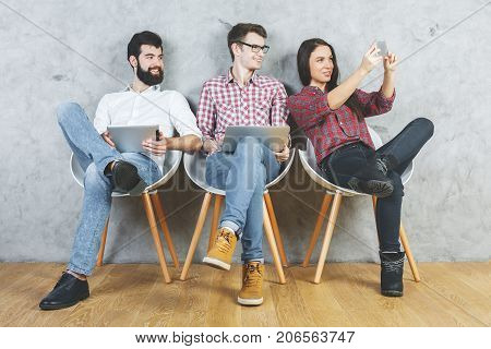 White adults sitting on chairs and using electronic gadgets. Concrete wall background. Technology communication teamwork and modern concept