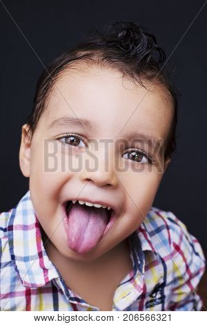 Playful little boy sticking out his tongue with smiling eyes over a dark background