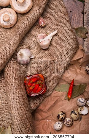 A top view of a composition of a jar of hot red peppers, fragrant garlic and quail eggs on a brown fabric and on a wooden background. Mushrooms, green bay leaves and rosemary on a paper and on a desk.