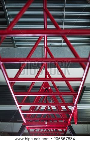 Close-up of crimson cylindrical metal, steel bars that are rigidly held above and parallel to the floor on a light silver background, equipment for sports competitions. Stairway for sports exercises.