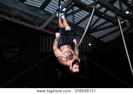 Cross Fit Bearded Tattooed Man Doing Dipping Exercise On Fitness Dip Rings At Gym, Full Length. Fitn