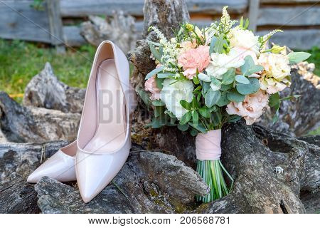 Close Up Of Beautiful Wedding Bouquet Of Pink And White Roses Standing Near Bride Shoes On Wood Stum
