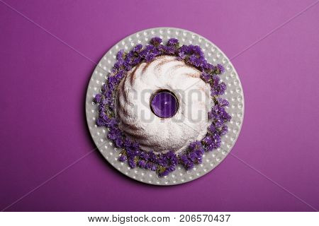 A plate with little purple flowers, a ring cake covered with powdered sugar, a piping hot bakery product for celebrations on a bright violet background, top view.