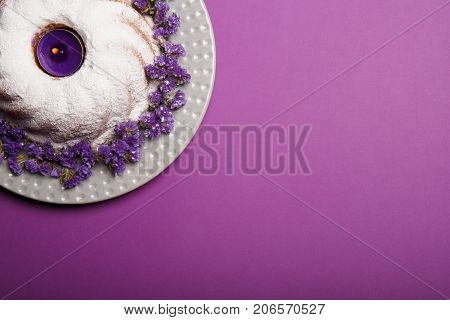 A ring cake covered with powdered sugar on a plate decorated with little purple flowers and a lit candle on a bright violet background, copy space, top view.