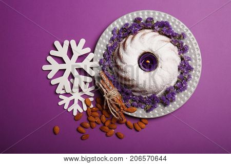 Top view of a plate with a round cake covered with powdered sugar and decorated with little flowers, almond, sticks ok cinnamon and white snowflakes on a bright violet background. Christmas concept.