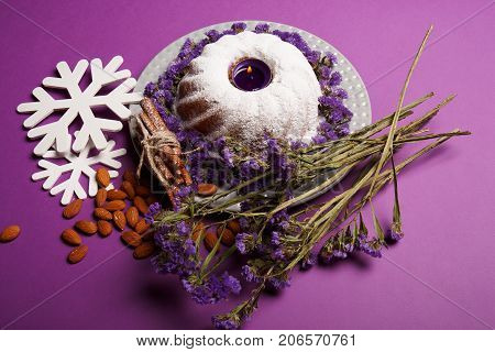 A ring cake sprinkled with powdered sugar, a lighted candle in the center, almond, white snowflakes, sticks of cinnamon on a bright violet background, top view. Winter holiday concept.