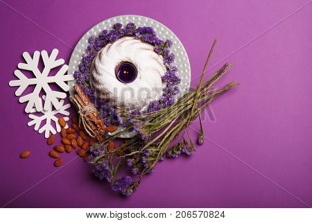 Top view of snowflakes, almond, sticks of cinnamon, a bouquet of little purple flowers, a plate of a round cake sprinkled with powdered sugar, a candle on a bright violet background. Holiday concept.