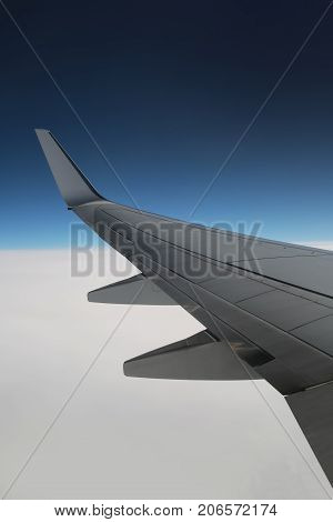 Aircraft wing on the clouds Flying background vertical. Beautiful view from plane through aircraft window. Beautiful blue sky and white clouds smoke for calm flight