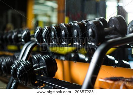 Iron dumbbells, equipment for weight lifting, gym, weight training, workouts, routines, increasing strength and size of muscles on a dark blurred background.