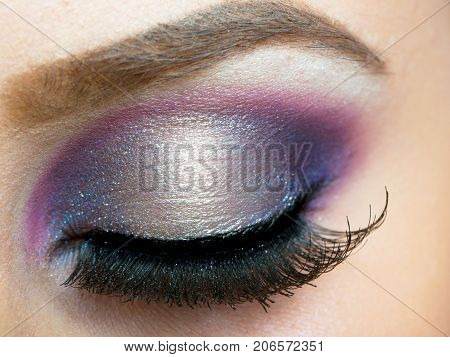 Female eye makeup with pink and purple beautiful shadows and long false eyelashes. Closed girl's eye with an evening make-up