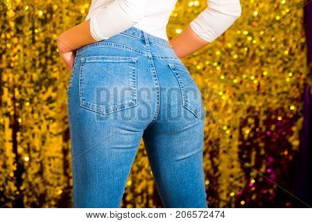 Sexy woman buttocks in denim with a beautiful waist. Perfect female ass in jeans briefs on the gold background. Fit slim female butt in blue jeans. Pretty sexy model with amazing body. Hot buttocks