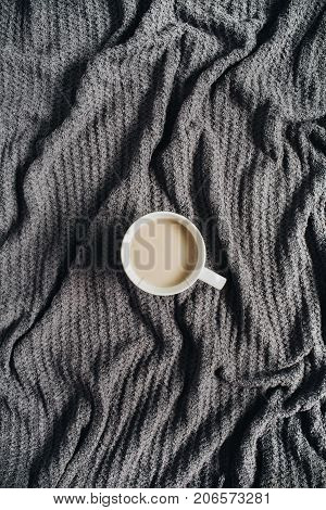 Coffee with milk on warm terry plaid. Flat lay top view minimal background.