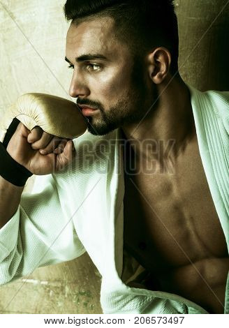 Man winner in boxing gloves, karate suit and accessories. Bearded attractive man boxer in bathrobe with shaved bare chest. Sexy handsome brunette with stylish hair. Strong healthy Athletic Man Fitness