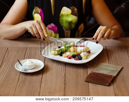 Sweet, soft, thin, organic pancakes with fresh spicy mint, sugar powder, and many sliced berries in a plate on a cafeteria background. A girl eating fruity and creamy pancakes with fork and knife.
