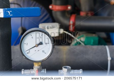 A device for measuring pressure or a pressure gauge on the background of the piping and handle. Design in modular design. The pressure gauge is round with an arrow and numbers.