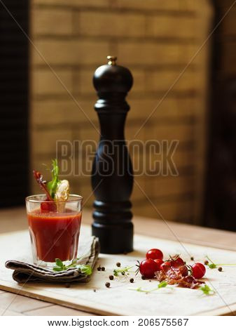 A glass of Bloody Mary or Bloody Caesar and cherry tomatoes on a white fabric and on a wooden table. Stylish pepper mill and alcohol cocktail with bacon on a top of the glass on a blurred background.