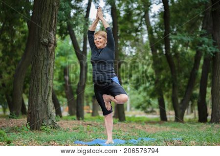 Joyful, gorgeous, happy elderly woman in comfortable sportswear, practicing yoga on a mat on a blurred perk background. Copy space.