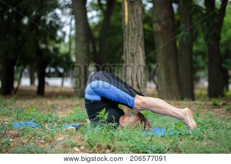 Amazing senior lady doing difficult yoga workout on a blurred natural background. Strong, healthy, muscular old woman doing fitness.