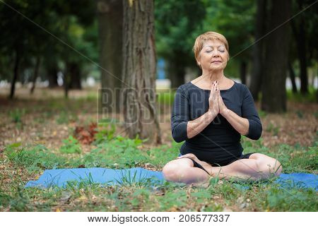 Peaceful, focused, happy senior woman meditating in a lotus position on a mat on a blurred garden or park background. Copy space.