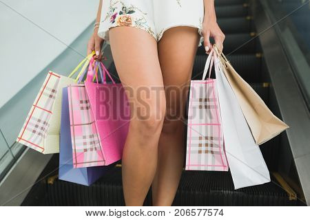 Body parts image, lady's legs doing shopping. Sale in the city, consumerism and people concept - happy young woman with shopping bags walking in mall, bags by store. Buying clothes.