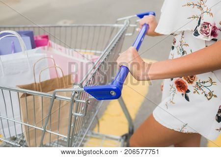 Stylish female photo while walking along the street. Business, sale and business concept, soft focus. Close-up of beautiful woman in white costume with many shopping bags.
