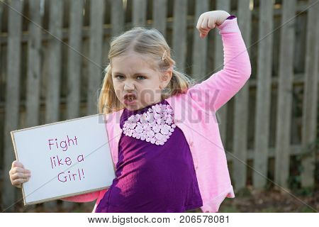 adorable school age girl wearing pink and holding sign that says fight like a girl for women's rights