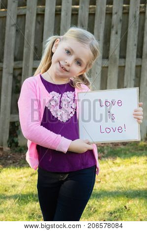 adorable school age girl wearing pink and holding sign that says love is love for women and gay rights