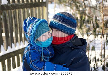 adorable father and sun snuggling together to keep warm while wearing winter clothes outside in the snow