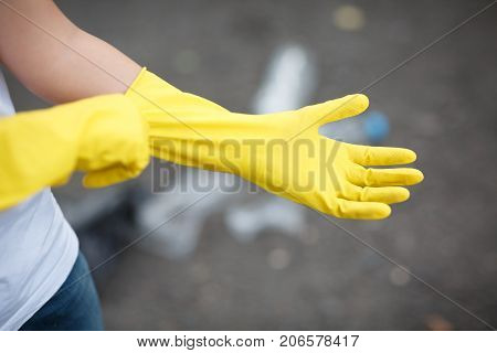Outdoors cleaning. Environmental protection. Closeup cropped portrait. Getting started cleaning. Yellow rubber cleaning gloves closeup. Workhouse concept. Homework, washing and cleaning of the theme.