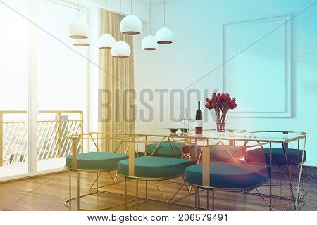 Corner of a white cafe interior with a wooden floor a glass table and blue chairs standing near it. There is a panoramic window and a poster on the wall. 3d rendering mock up toned image