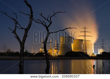 Dramatic shot of a coal-fired power station at night with dead trees in a lake in the foreground.
