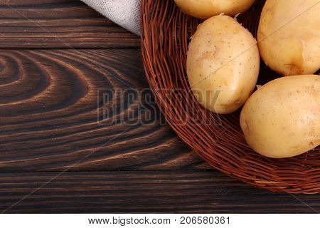 Close-up of new potatoes in a wicker wooden plate, health-giving vegetables for palatable summer dishes on a dark brown background. Harvest of vegetables.